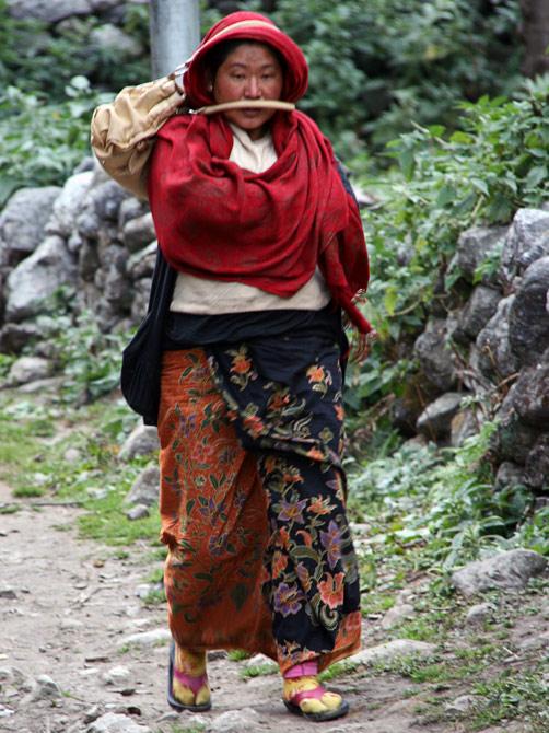 Непальская женщина несет сумку на голове