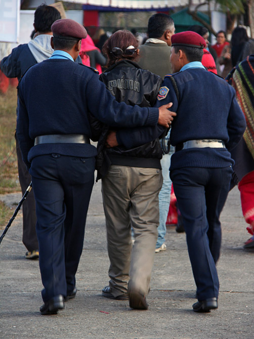 Полиция уводит пьяницу с уличного фестиваля в Покхаре, Непал