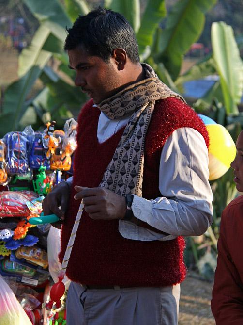Нарядный продавец игрушек на уличном фестивале в Покхаре, Непал