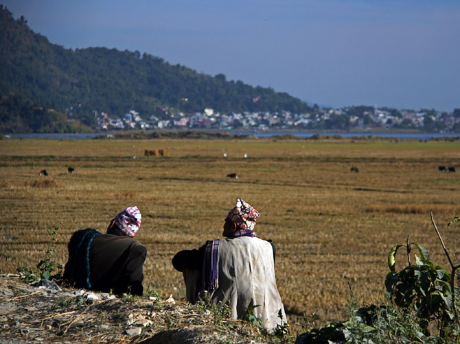 Двое непальцев любуются видом на озеро и город Покхара, Непал