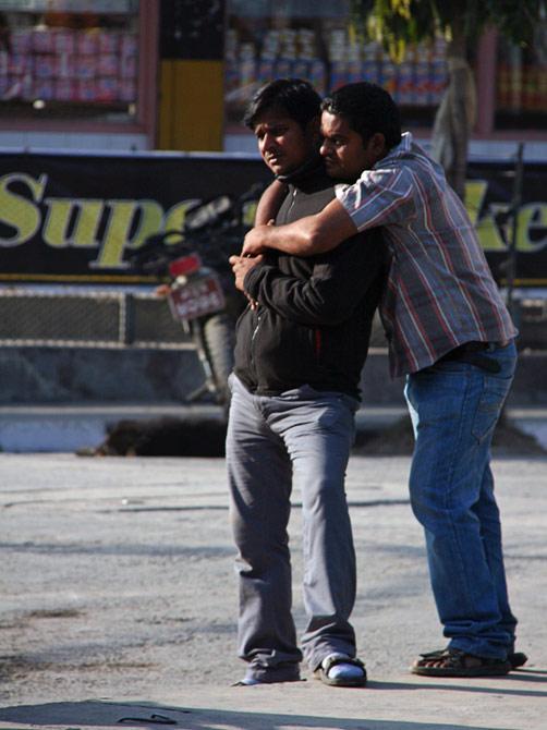 Двое непальских парней обнимаются на уличном фестивале в Покхаре, Непал