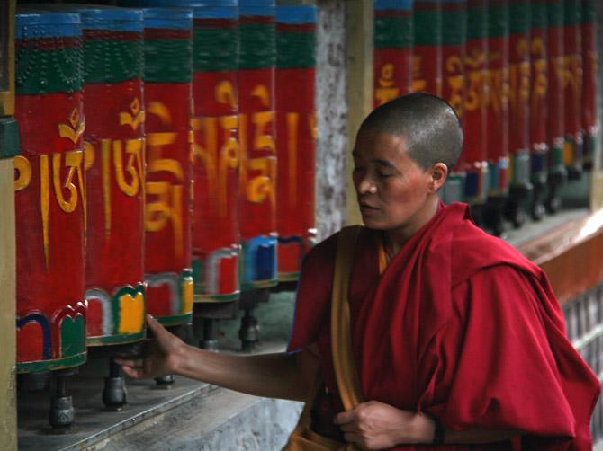 Буддистская монахиня крутит молельные колеса, Маклеод Ганж, Дарамсала, Индия