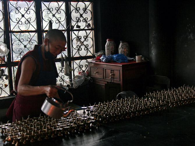 Монахиня наполняет свечи маслом в храме Маклеод Ганжа, Дарамсала, Индия