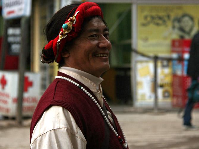 Тибетец в национальном костюме на улице Маклеод Ганжа, Дарамсала, Индия