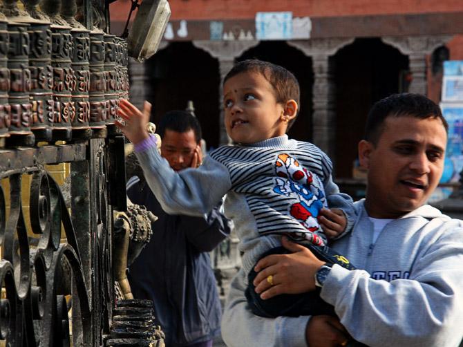 Ребенок вращает молельные колеса, Катманду, Непал