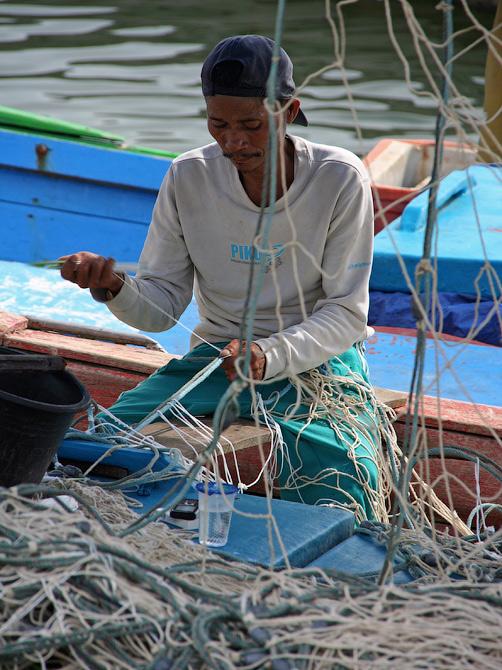Рыбак чинит сети в порту Банда Аче, Суматра, Индонезия