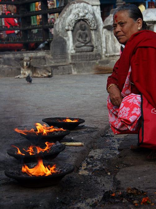 Сваямбу - женщина у ритуальных огней, Катманду, Непал